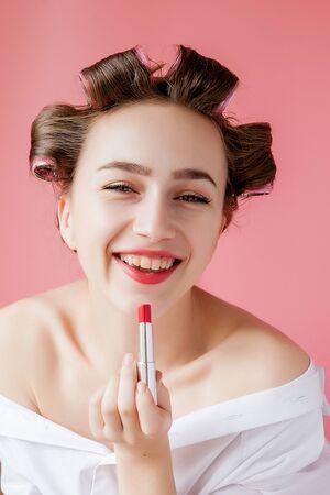 Closeup portrait of beautiful girl putting on red lipstick. Фото со стока