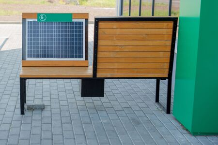 Outdoor shot of wooden bench in park having solar power panel installed, USB cabel connected to smartphone.