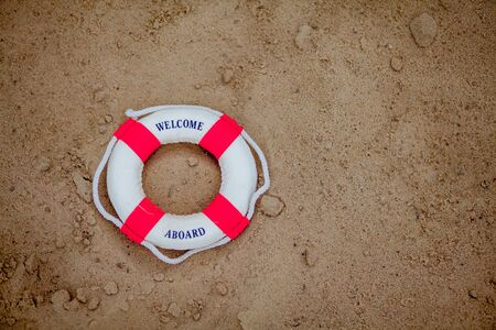 Close-up Of Miniature Lifebuoy Dig In The Sand At Beach. Archivio Fotografico - 129147347