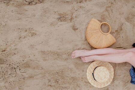 Woman tanned legs, straw hat and bag on sand beach. Travel concept. Relaxing at a beach, with your feet on the sand Standard-Bild - 129147414