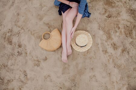 Woman tanned legs, straw hat and bag on sand beach. Travel concept. Relaxing at a beach, with your feet on the sand Standard-Bild - 129010149