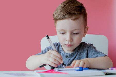 Retrato de niño lindo niño en casa haciendo los deberes. Niño pequeño concentrado escribiendo con lápiz de colores, en el interior. Escuela primaria y educación. Niño aprendiendo a escribir letras y números. Foto de archivo