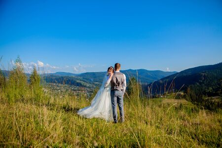 Newlyweds smile and hug each other among the meadow on top of the mountain. Wedding walk in the woods in the mountains, the gentle emotions of the couple, photo for Valentines Day. Stock Photo