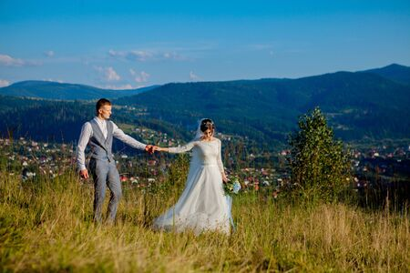 Newlyweds smile and hug each other among the meadow on top of the mountain. Wedding walk in the woods in the mountains, the gentle emotions of the couple, photo for Valentine's Day. Stock Photo - 130204700
