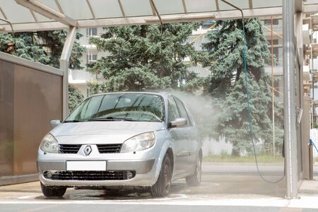 Kyiv, Ukraine- May 15, 2019 Manual car wash with pressurized water in car wash outside.