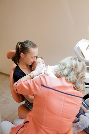 Mom and her little son visiting the dentist. Stock Photo - 129846176