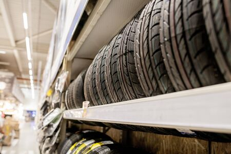 Rack with variety of car tires in automobile store. Фото со стока