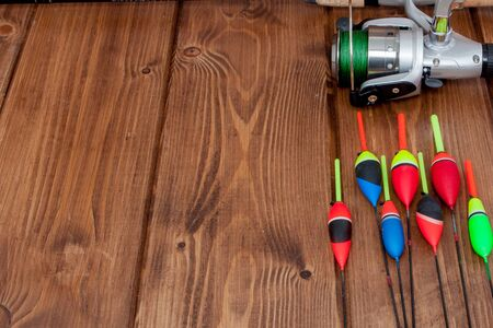 Fishing tackle - fishing rod fishing float and lures on beautiful blue wooden background, copy space. 스톡 콘텐츠