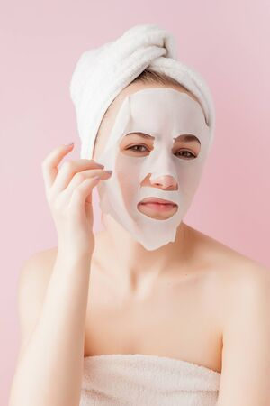 Beautiful young woman is applying a cosmetic tissue mask on a face on a pink background.