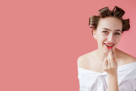 Closeup portrait of beautiful girl putting on red lipstick. Stock Photo