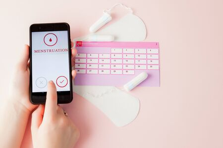 Tampon, feminine, sanitary pads for critical days, feminine calendar, pain pills during menstruation on a pink background. Tracking the menstrual cycle and ovulation. Stock Photo
