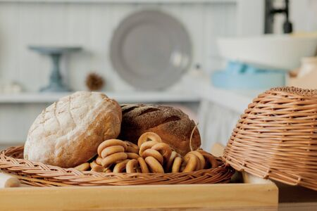 Assortment of breads near a wicker basket on a table in a rustic kitchen. Composition in kitchen at the photo studio. Stock fotó