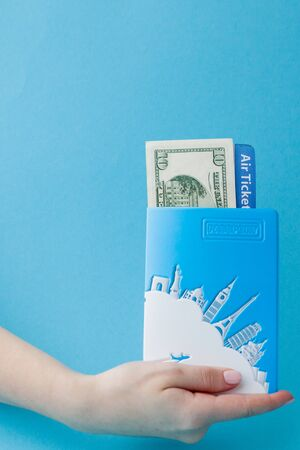 Passport, dollars and air ticket in woman hand on a blue background. Travel concept, copy space. Stock Photo