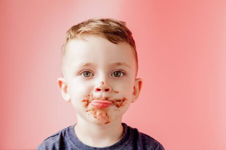 Little boy eating donut chocolate. Cute happy boy smeared with chocolate around his mouth. Child concept