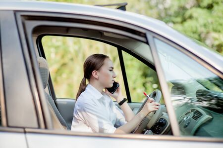 Picture of young businesswoman speaks by phone and doing makeup while driving a car in the traffic jam.
