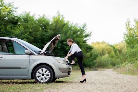 Mujer joven junto a la carretera después de que su automóvil se descompuso. Abrió el capó para ver los daños. Foto de archivo