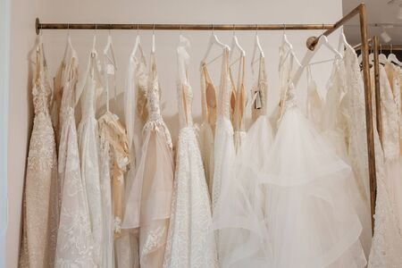 Assortment of dresses hanging on a hanger on the background studio. Fashion wedding trends. Interior of wedding shop.