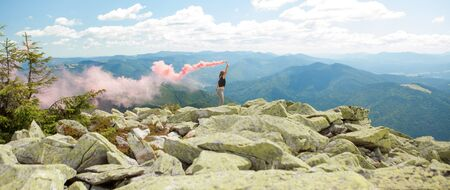 Beautiful woman with red colored smoke at the top of the mountain and cloudy sky background.
