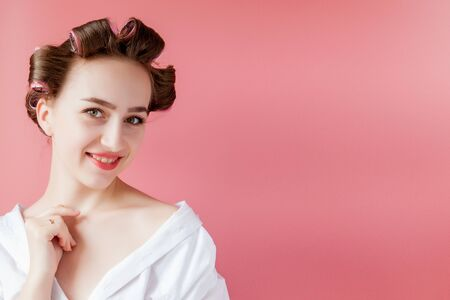 Beautiful girl in hair curlers on pink background.