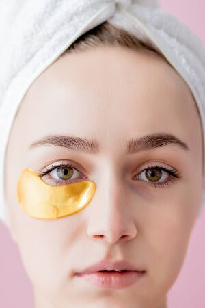 Portrait of Beauty Woman with Eye Patches on pink background. Woman Beauty Face with Mask under Eyes. Beautiful Female with natural Makeup and Gold Cosmetics Collagen Patches on Fresh Facial Skin. Stock Photo