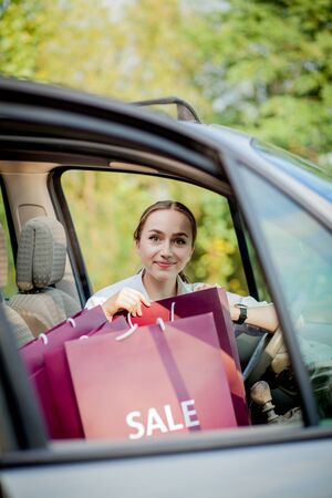 Woman with her shopping bags into the car - shopping concept