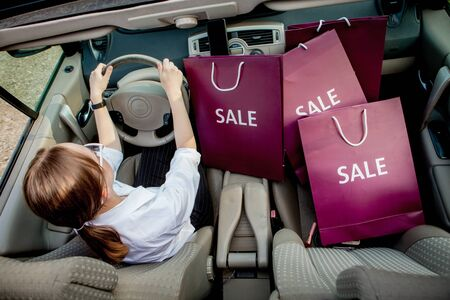A girl with shopping bags is driving a car, concept of discounts and shopping, top view. 写真素材