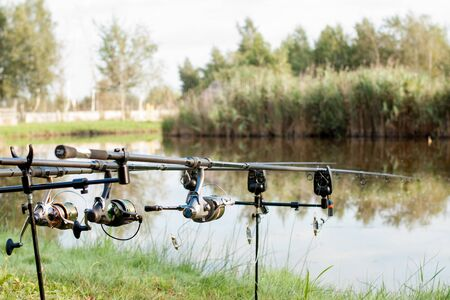 Closeup of a reel fishing rod on a prop and water background.