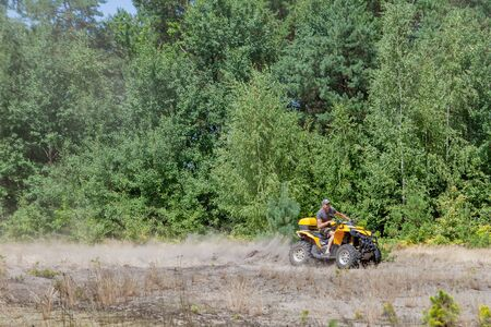 Man riding a yellow quad ATV all terrain vehicle on a sandy forest. Extreme sport motion, adventure, tourist attraction Reklamní fotografie