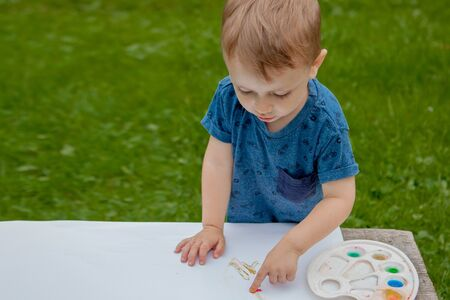Cute little boy painting with a paint hands using gauche paints
