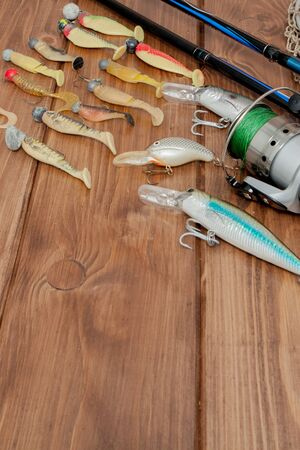Fishing tackle - fishing spinning, hooks and lures on wooden background with copy space. 스톡 콘텐츠