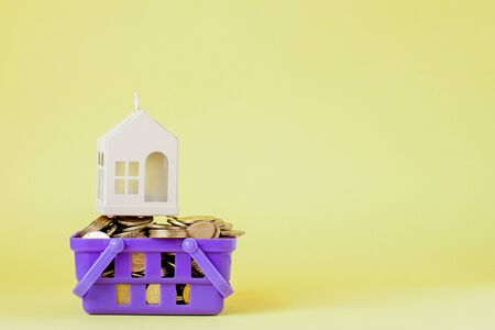 Model house and coin in shopping basket concept for mortgage saving on yellow background.
