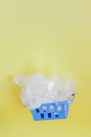 polythene bags in shopping basket on yellow background. 写真素材