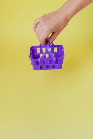 Buying things at market shops concept. Woman hand holding small tiny shopping basket trolley over trend yellow background 写真素材