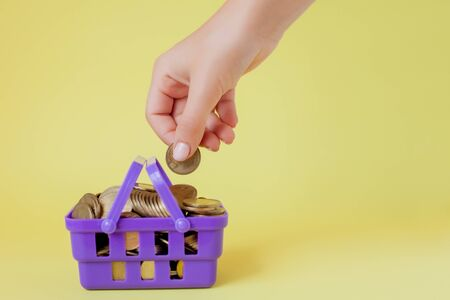 Hand holding a coin with pile of coin in the shopping basket on yellow background. 写真素材