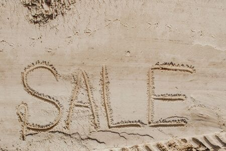 The word sale is painted on the sand. Beach background. View from above. The concept of summer, summer kanikkuly, vacation, holydays