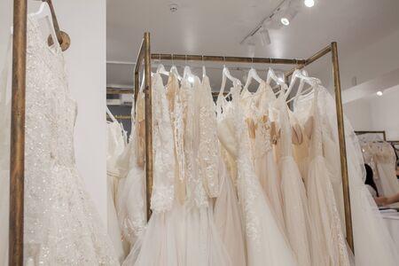 Asortyment sukienek wiszących na wieszaku na tle studia. Trendy w modzie ślubnej. Wnętrze sklepu ślubnego.