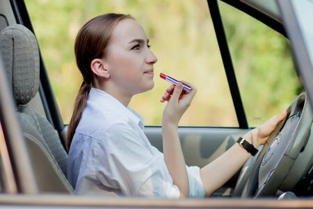 Picture of young businesswoman doing makeup while driving a car in the traffic jam.