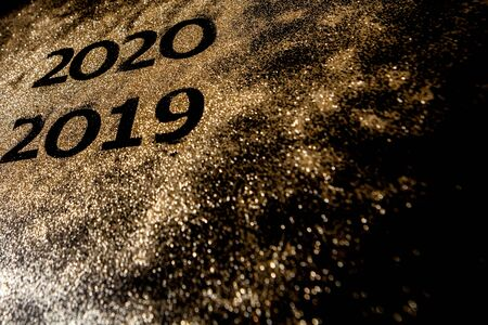 Beautiful sparkling Golden Numbers of 2019 to 2020 on black background for design, happy new year concept. Stock Photo