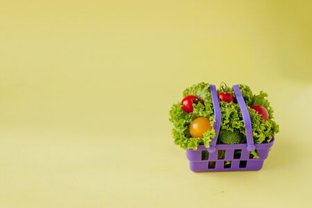 Small Fresh vegetables in basket on yellow background. Food background concept with copyspace. Reklamní fotografie - 132190957