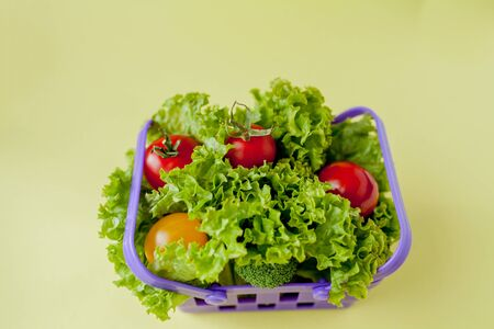 Small Fresh vegetables in basket on yellow background. Food background concept with copyspace. Reklamní fotografie - 132190901
