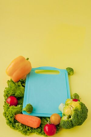 Blackboard with fresh vegetables on yellow background. Concept of Healthy Eating.