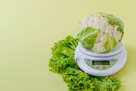 Organic cauliflower on a vase on a yellow background. Healthy eating, diet planning, weight loss, detox, organic farming concept