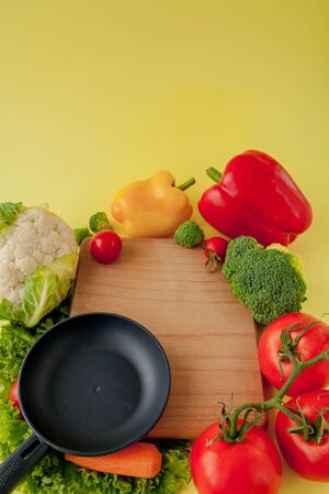 Variety of vegetables and frying pan on a blackboard, top view. Vegan and healthy concept