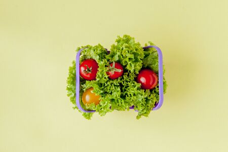 Small Fresh vegetables in basket on yellow background. Food background concept with copyspace. Reklamní fotografie - 132193305