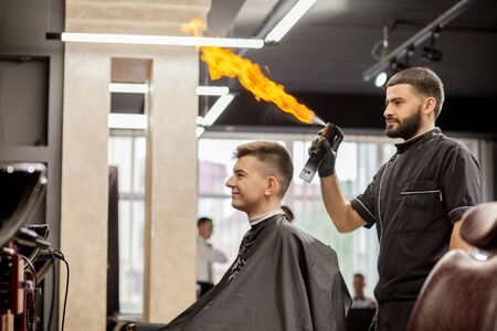 Brutal guy in modern Barber Shop. Hairdresser makes hairstyle a man . Master hairdresser does hairstyle with hair clipper. Concept barbershop.