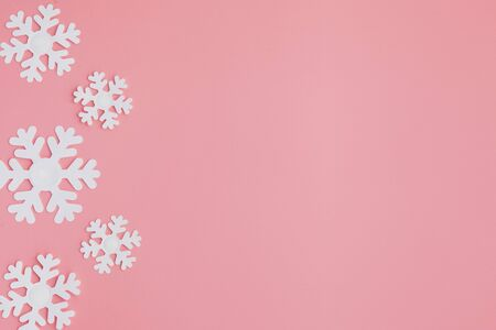 Winter pattern made of snowflakes and on pink background. Christmas concept. Flat lay. Copy space for your text.