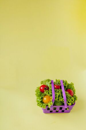 Small Fresh vegetables in basket on yellow background. Food background concept with copyspace.