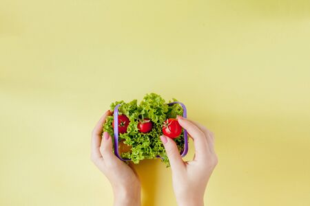 Hand holding fresh vegetables in basket on yellow background top view.
