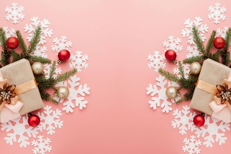 Close up shot of small gift wrapped with ribbon on pink background. Christmas background. Minimal concept. Flat lay. Top view. Stock Photo