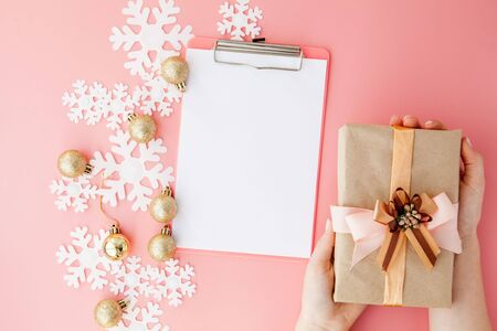 Christmas gift in womens hands and notebook on a pink background, a view from above.